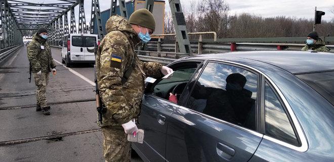Украинский пограничник проверяет документы во время карантина
